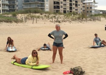 Instructors giving students surf lessons