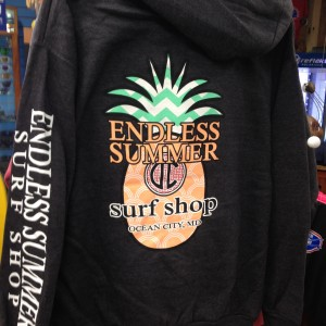 Black hooded sweatshirt with pineapple logo hanging up