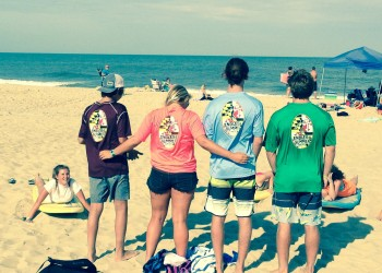 group of four showing the back of their endless summer shirts