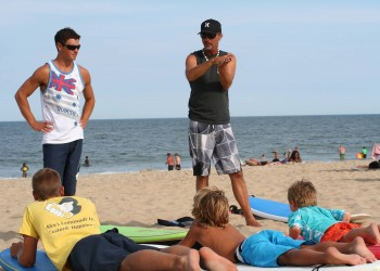 instructors explaining how to surf to kids in Ocean City MD