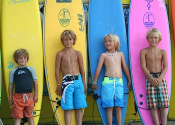 kids standing in front of different colored surfboards