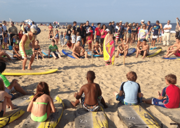 a group observing a man standing next to surfboard