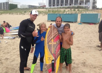 group of four posing for picture behind surfboard