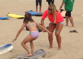 young girl being taught to surf in ocean city md