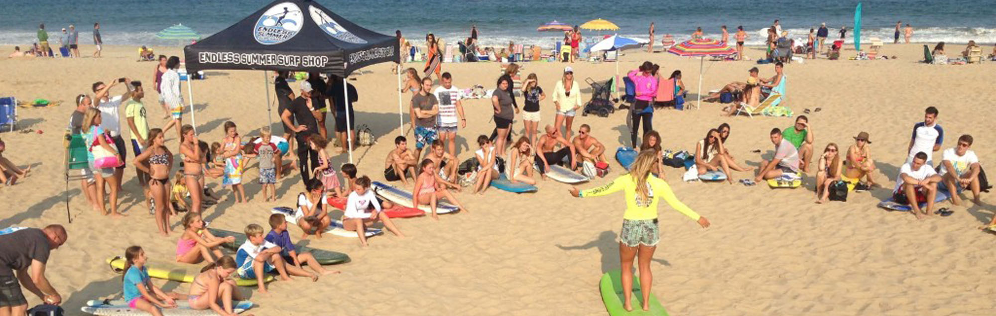 endless summer instructor giving surf lesson to crowd of kids