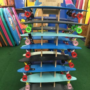 colorful surf shop penny longboards stacked on shelf