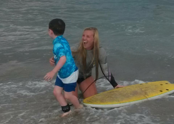 endless summer surf instructor giving young boy surf lesson